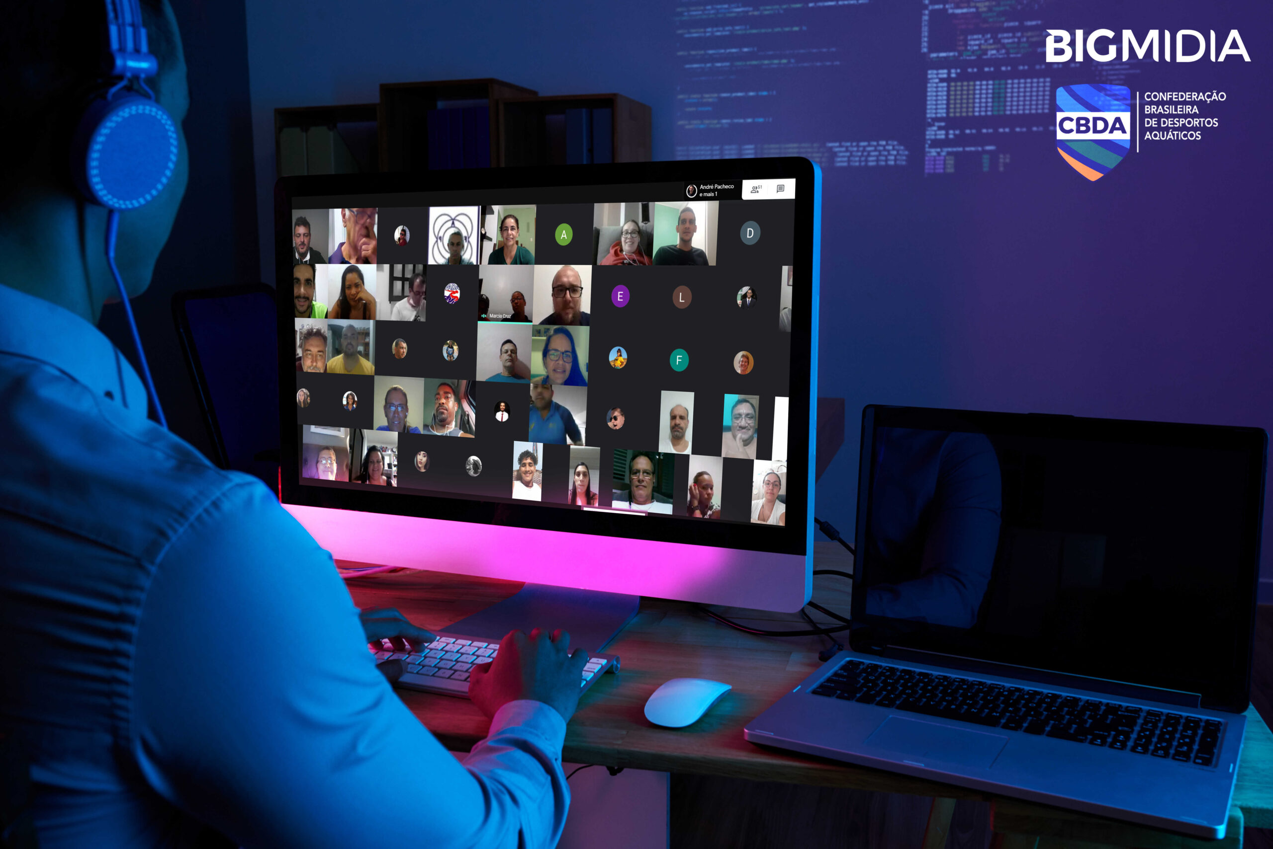 Imagem com uma pessoa de frente para um computador. Na tela do computador estão os participantes do curso online da Bigmidia.