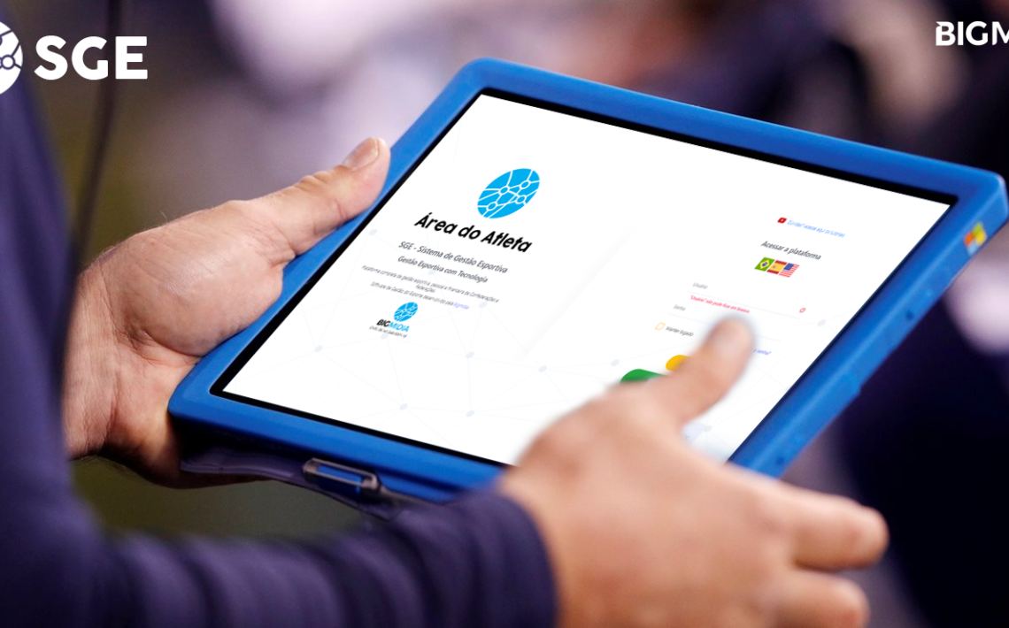 Pessoa com tablet na mão e na tela o sistema de login para atletas do software da Bigmidia