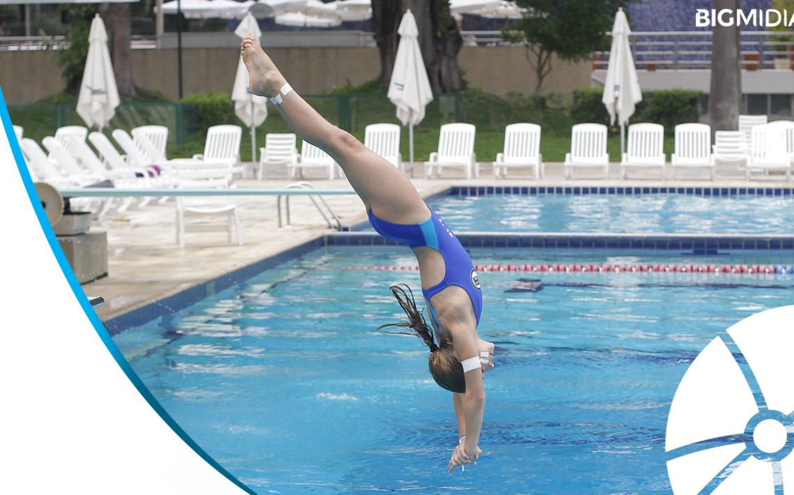 Foto de uma atleta dando um salto ornamental em piscina