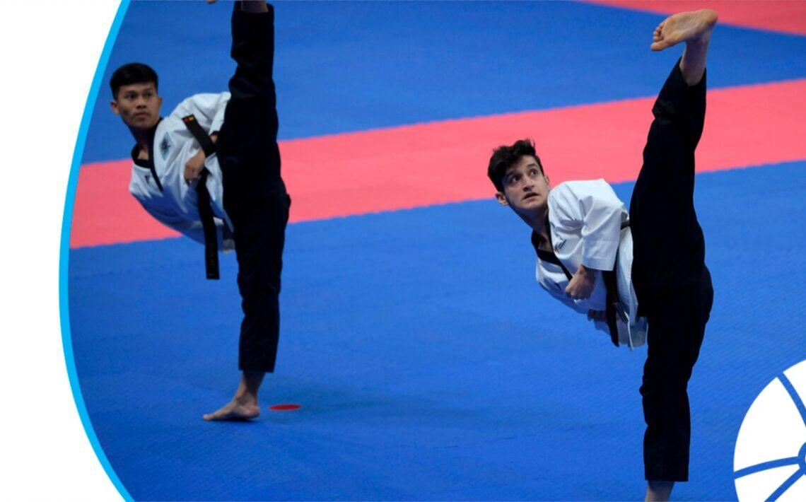 Dois jovens em um tatame azul realizando uma apresentação de Taekwondo
