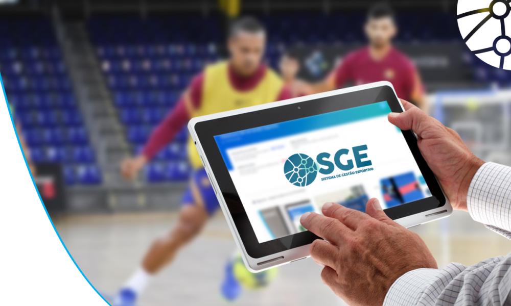 Atletas jogando Futsal com uma pessoa segurando um tablet com o Sistema de Gestão Esportiva na tela