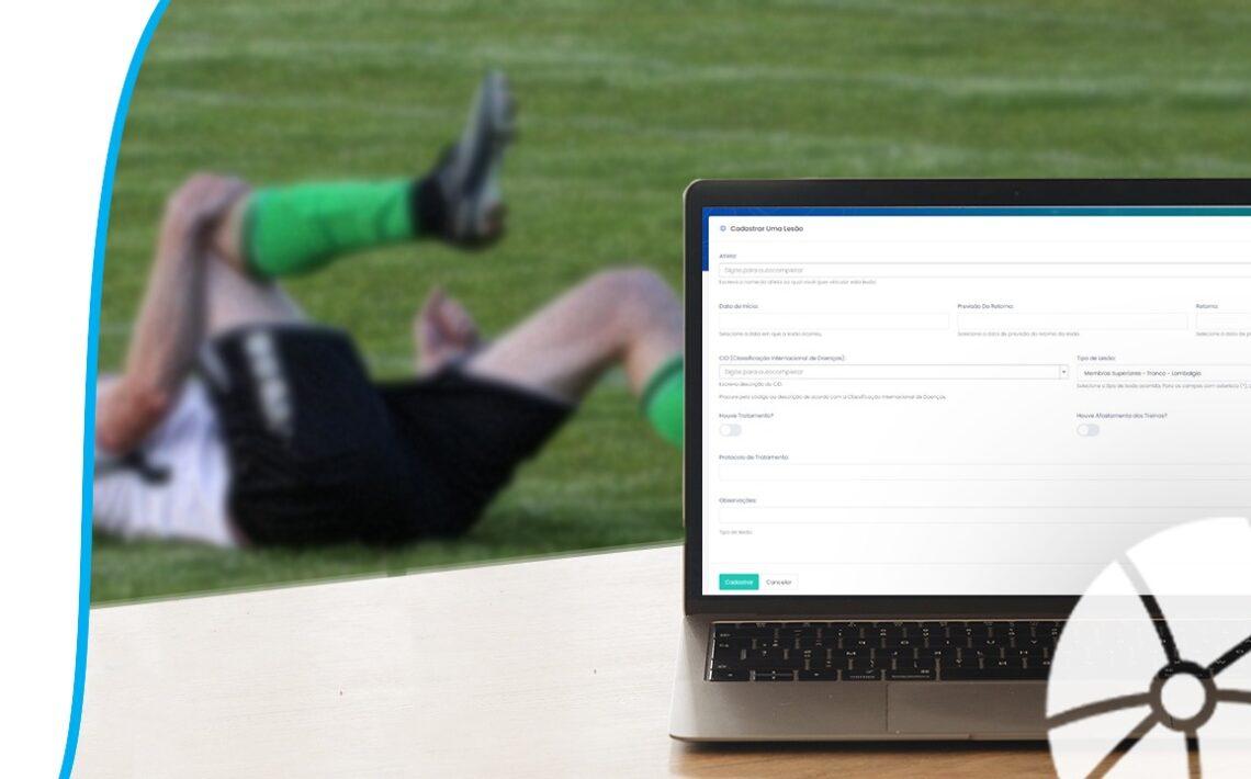Computador com o sistema de controle de lesões na tela. Ao fundo, um atleta contundido com a mão no joelho