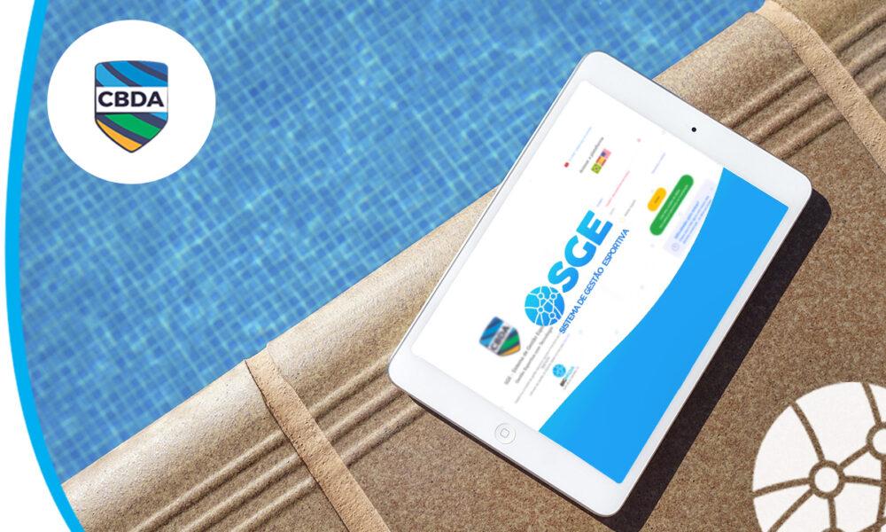 Tablet com o SGE da CBDA aberto na tela e uma piscina ao fundo